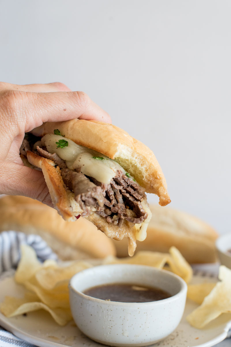 Close up picture of an Instant Pot french dip sandwich topped with cheese and held over a bowl of au jus