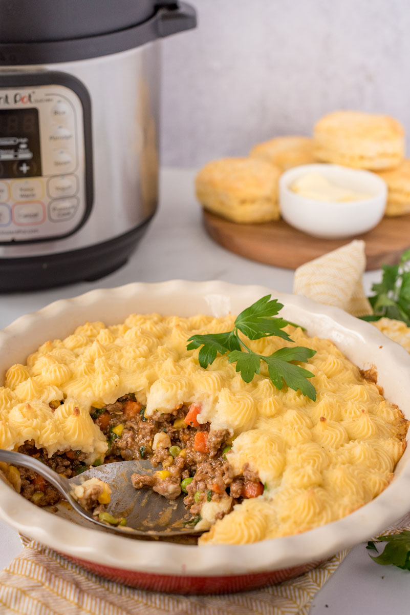 Shepherds pie made in an Instant Pot scooped out of the serving dish and placed in front of biscuits and an Instant Pot.
