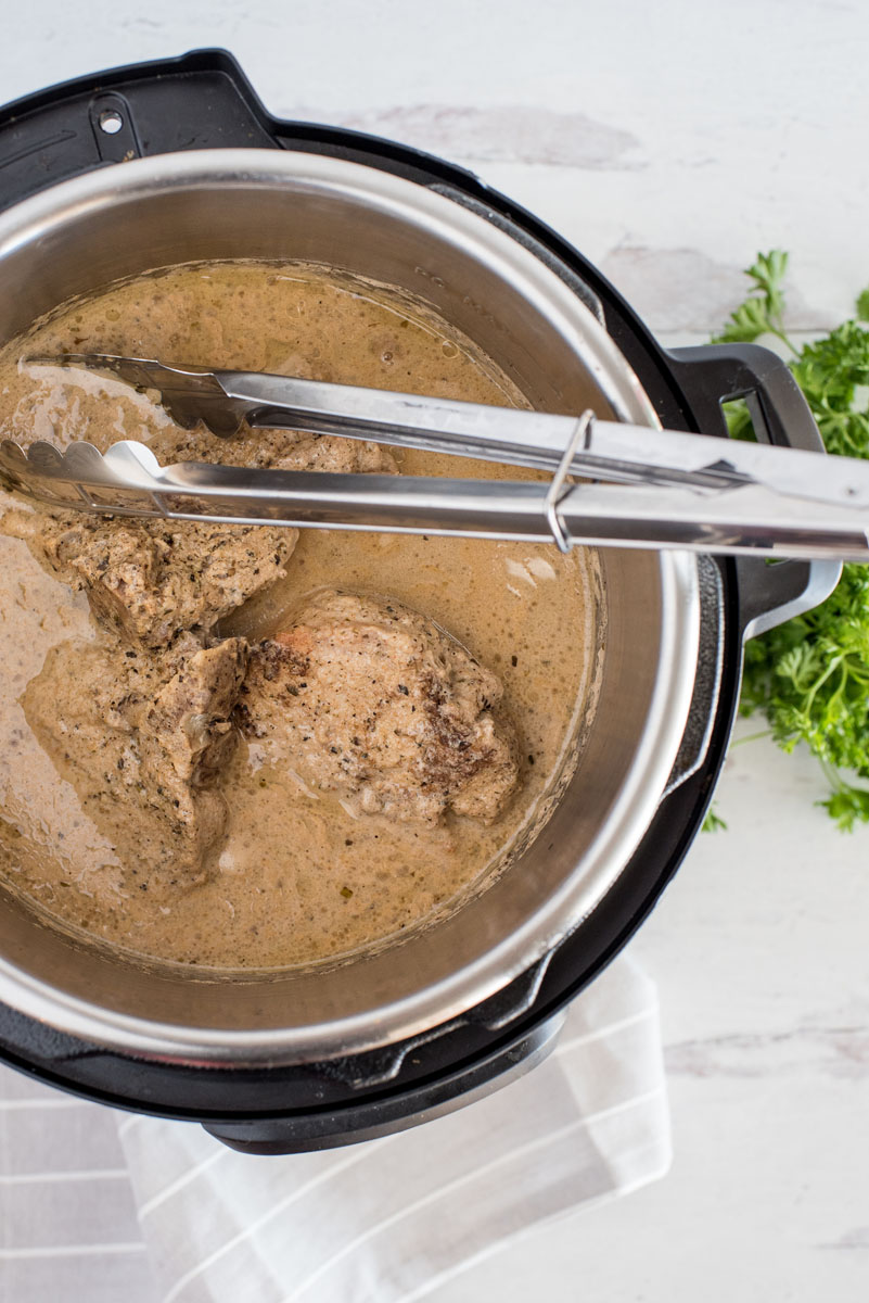 removing pork chops from an instant pot with metal tongs