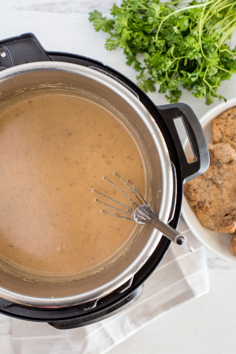 overhead of an instant pot with creamy mushroom gravy being whisked