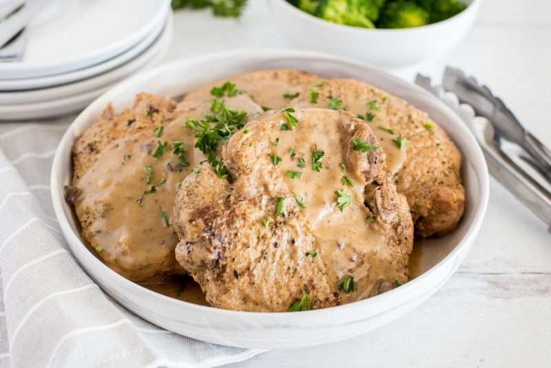 close up on a whitee bowl with four pork chops in mushroom gravy with steamed broccoli in the background