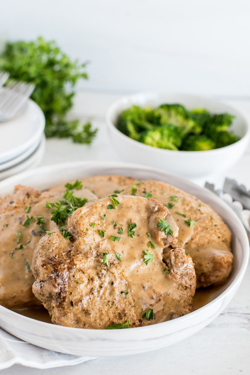 close up on a white bowl with four pork chops in mushroom gravy with steamed broccoli in the background