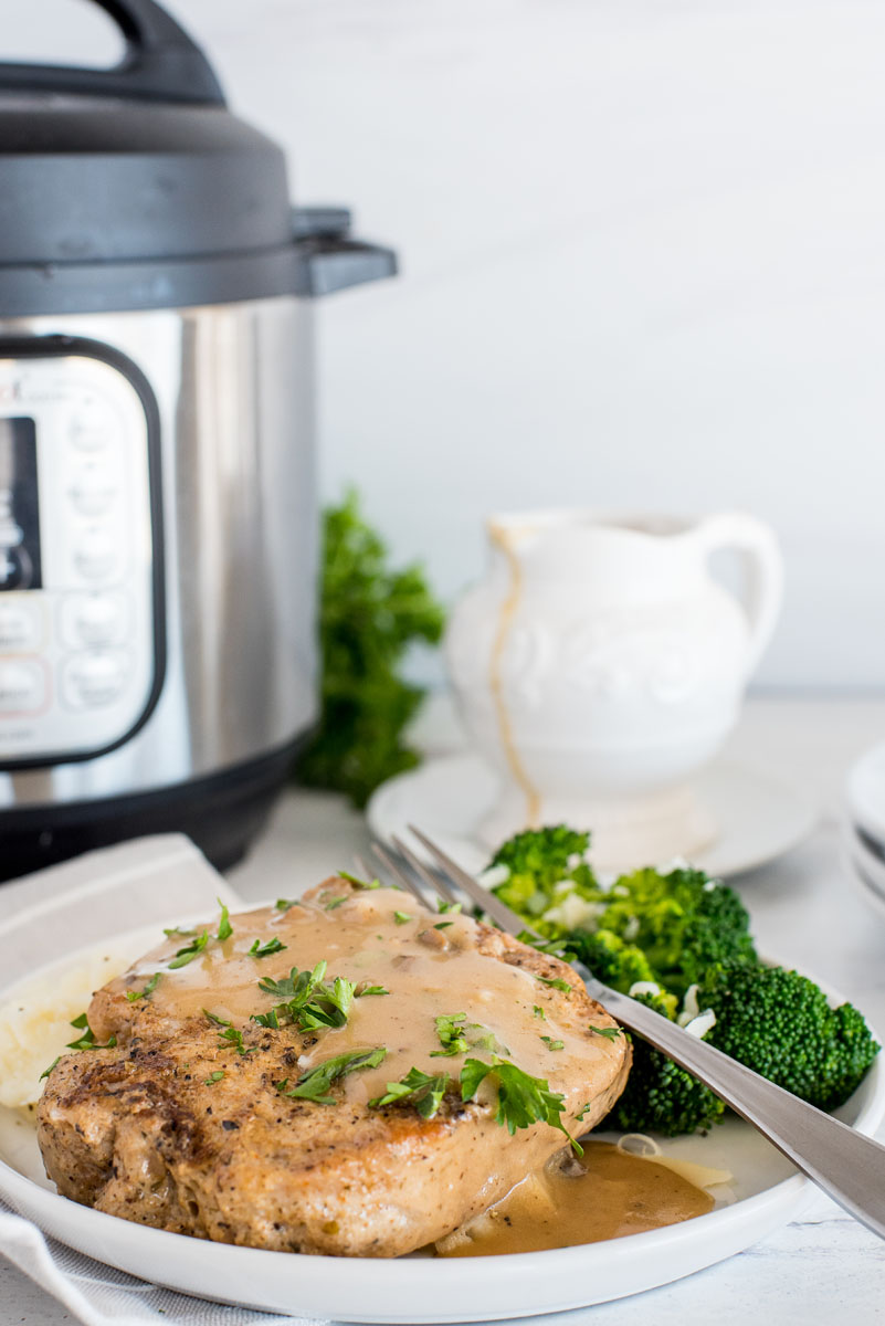 plate of pork chops with mushroom gravy in front of an electric pressure cooker