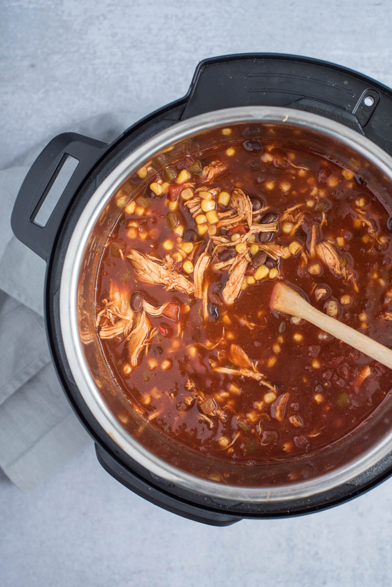 Chicken enchilada soup cooked in an Instant Pot with a wooden spoon for storing.