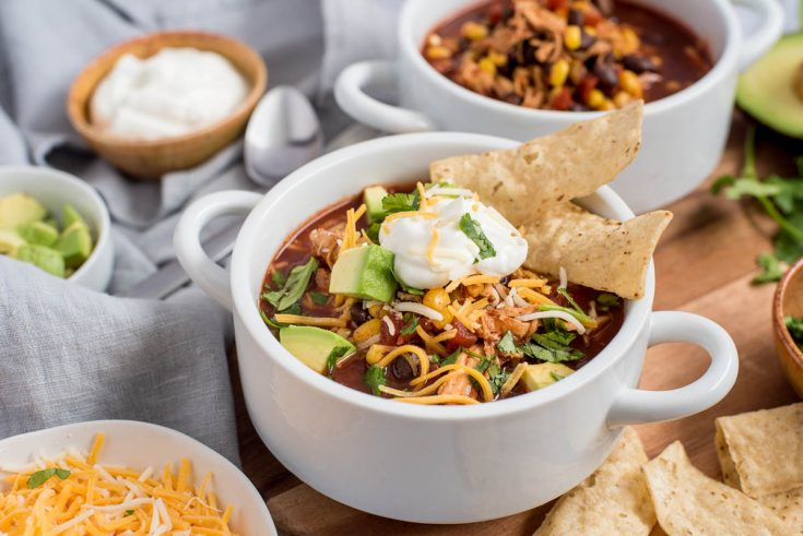 Close up shot of two bowls of Instant Pot chicken enchilada soup, one topped with cheese, sour cream, avocado, and chips, and the other without any toppings.