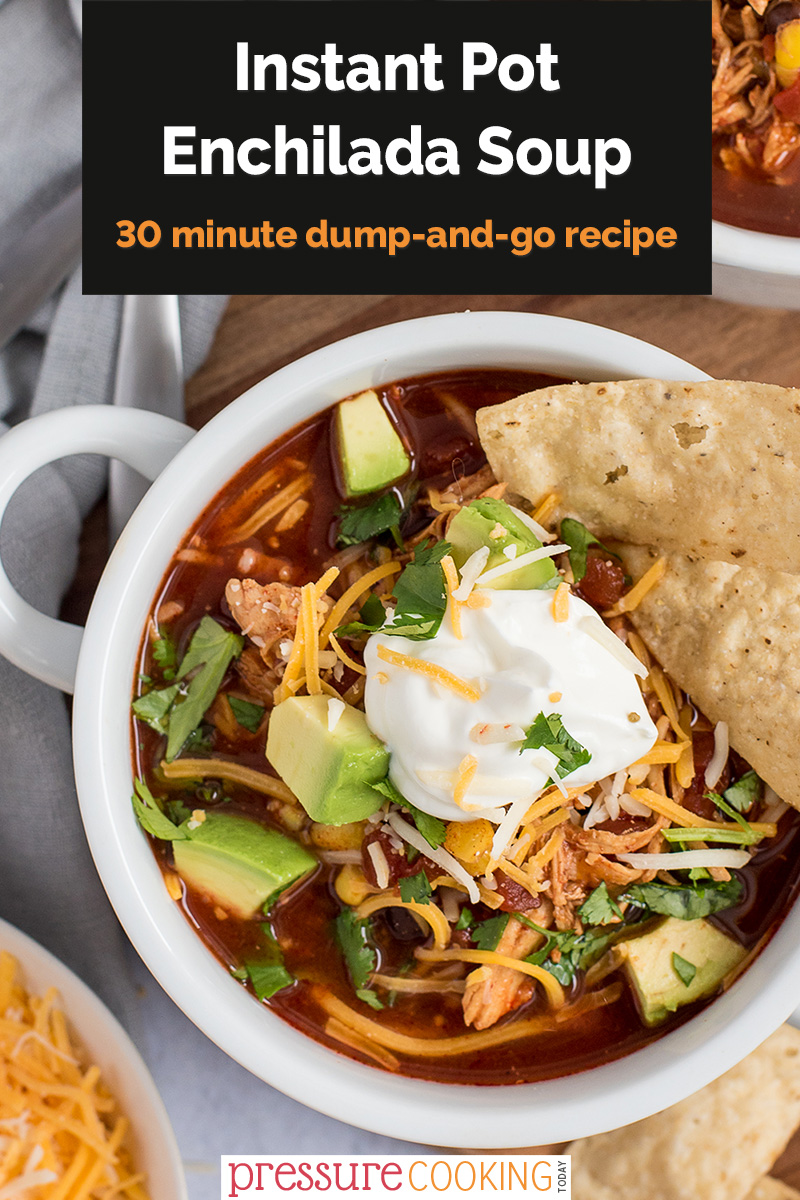 """Pinterest image with a black text box that reads """"Instant Pot Enchilada Soup: a 30-minute dump-and-go recipe"""", overlaid on a close-up overhead photo featuring chicken enchilada soup, with cilantro, avocados, shredded cheese, and tortilla chips via @PressureCook2da"""