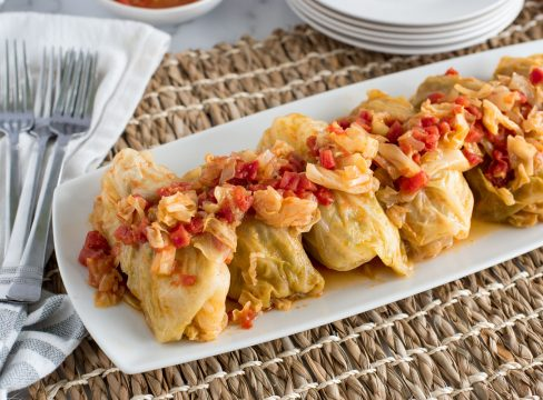 Stuffed Cabbage Rolls in a row, with red tomatoes and chopped cabbage in a sauce on top of the rolls, served on a white plate, with white napkins and a brown woven placemat underneath