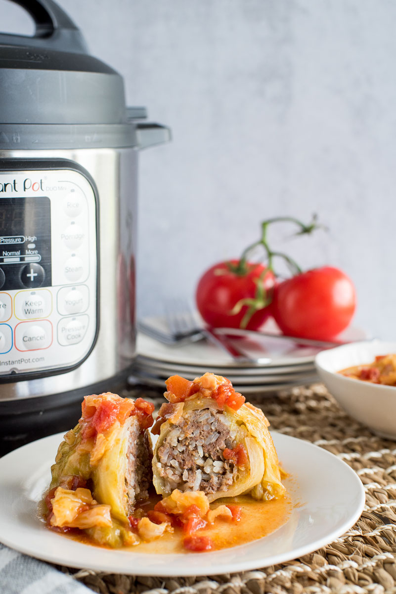 one stuffed cabbage roll cut in half on a plate with an instant pot in the background