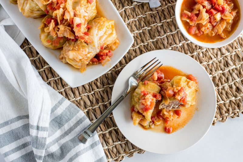 overhead of plates of stuffed cabbage rolls with a fork