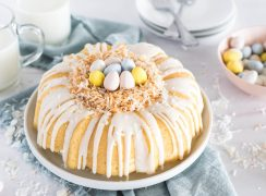 Instant Pot Coconut Bundt Cake, drizzled with white glaze and decorated with toasted coconut to look like a nest and Cadbury mini eggs on top, against a backdrop of a blue napkin and two classes of milk and a bowl of mini eggs in the background