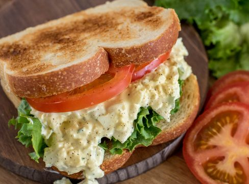 Close up picture of pressure cooker egg salad sandwich made with toasted bread, sliced tomato, and lettuce. Placed on a wooden cutting board.