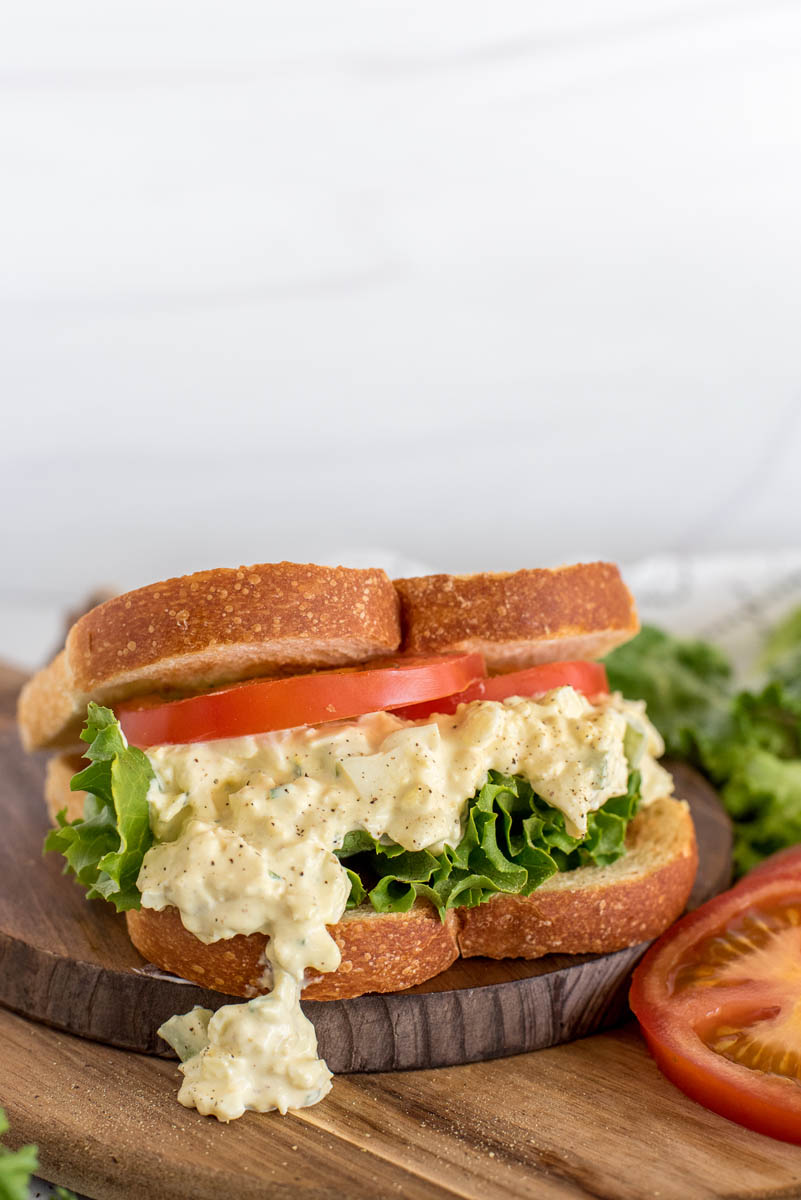 Instant Pot egg salad sandwich made on toasted bread with sliced tomatoes and lettuce. Placed on top of a wooden cutting board.