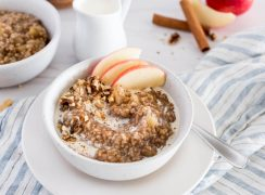 white bowl of apple-cinnamon flavored instant pot steel cut oats with apple slices, on top of a muted blue and white striped napkin with a glass of milk and a second bowl of steel cut oats in the background