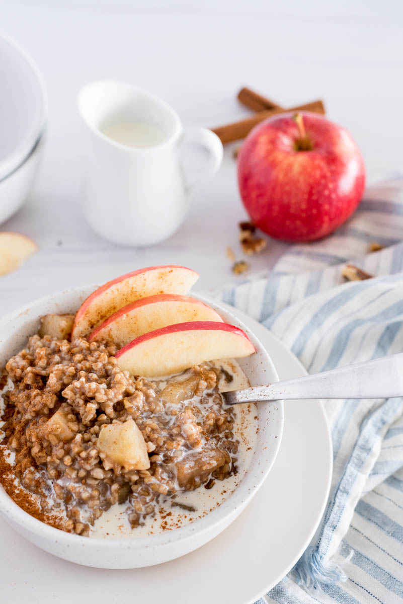 Close up picture of Instant Pot Cinnamon Apple Steel Cut Oats garnished with fresh sliced apples, in a white bowl, with a whole apple and a small pitcher of milk in the background.