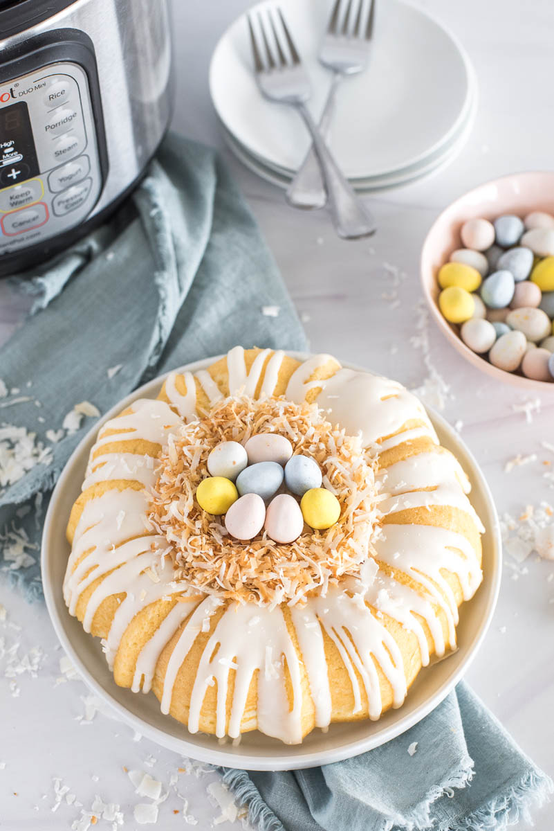 """An overhead shot of the Instant Pot coconut bundt cake dressed up for Easter, with a toasted coconut """"birds nest"""" in the middle center of the bundt, filled with pasted Cadbury Mini Eggs, with a blue napkin, white plates and forks, an Instant Pot, and a pastel pink bowl of Cadbury Mini Eggs visible in the background"""