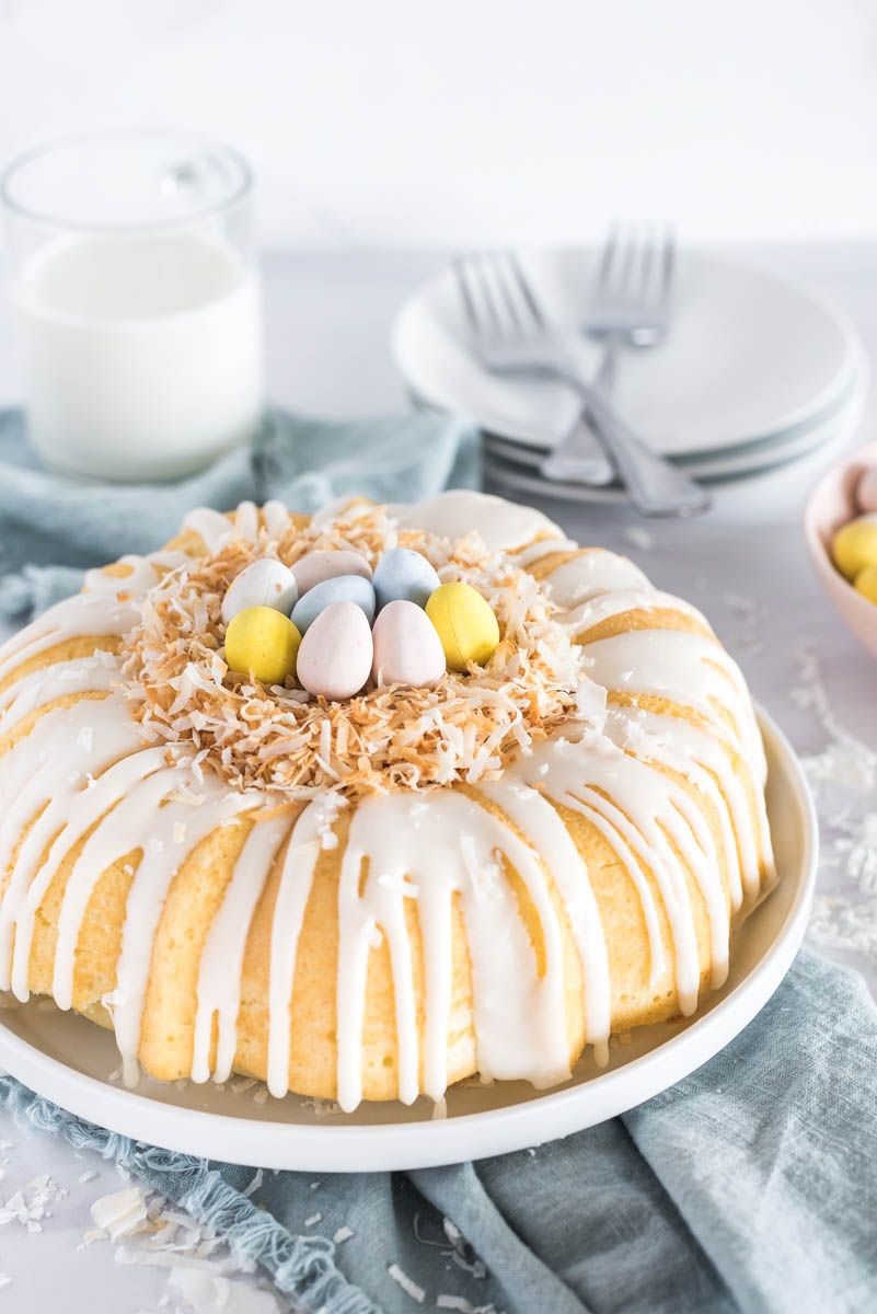 Coconut cake with the birds nest decoration in place on top, with a glass of milk and white plates and forks visible in the background