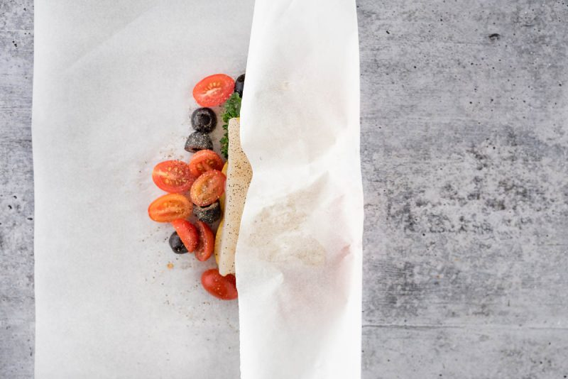 overhead of fish in parchment with the parchment folded over half