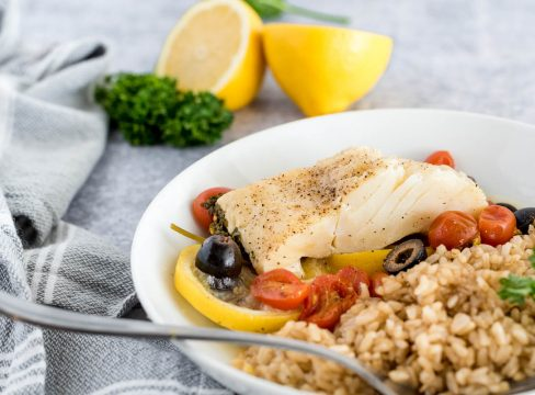 mediterranean fish on a white plate with brown rice and lemons