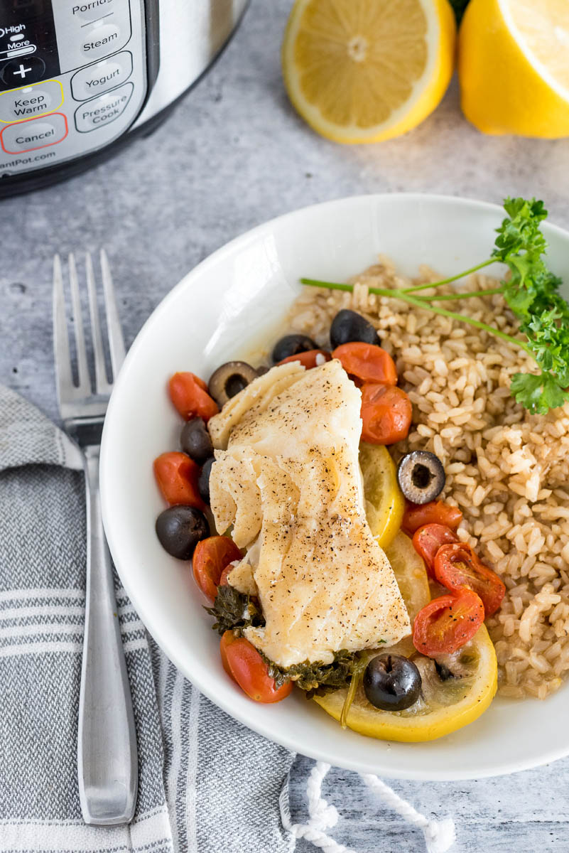 An overhead shot of Instant Pot Fish en Papillote on a white plate with tomatoes, olives and lemons visible underneath, served beside brown rice, with a fork, an Instant Pot, and lemons visible in the background