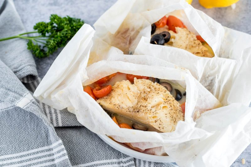 two parchment paper packets with fish fillets