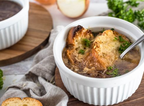 A finished serving of Instant Pot French Onion soup, with browned bread and melted cheese on top of a rich brown french onion soup., served in a white ramekin with a second bowl in the background