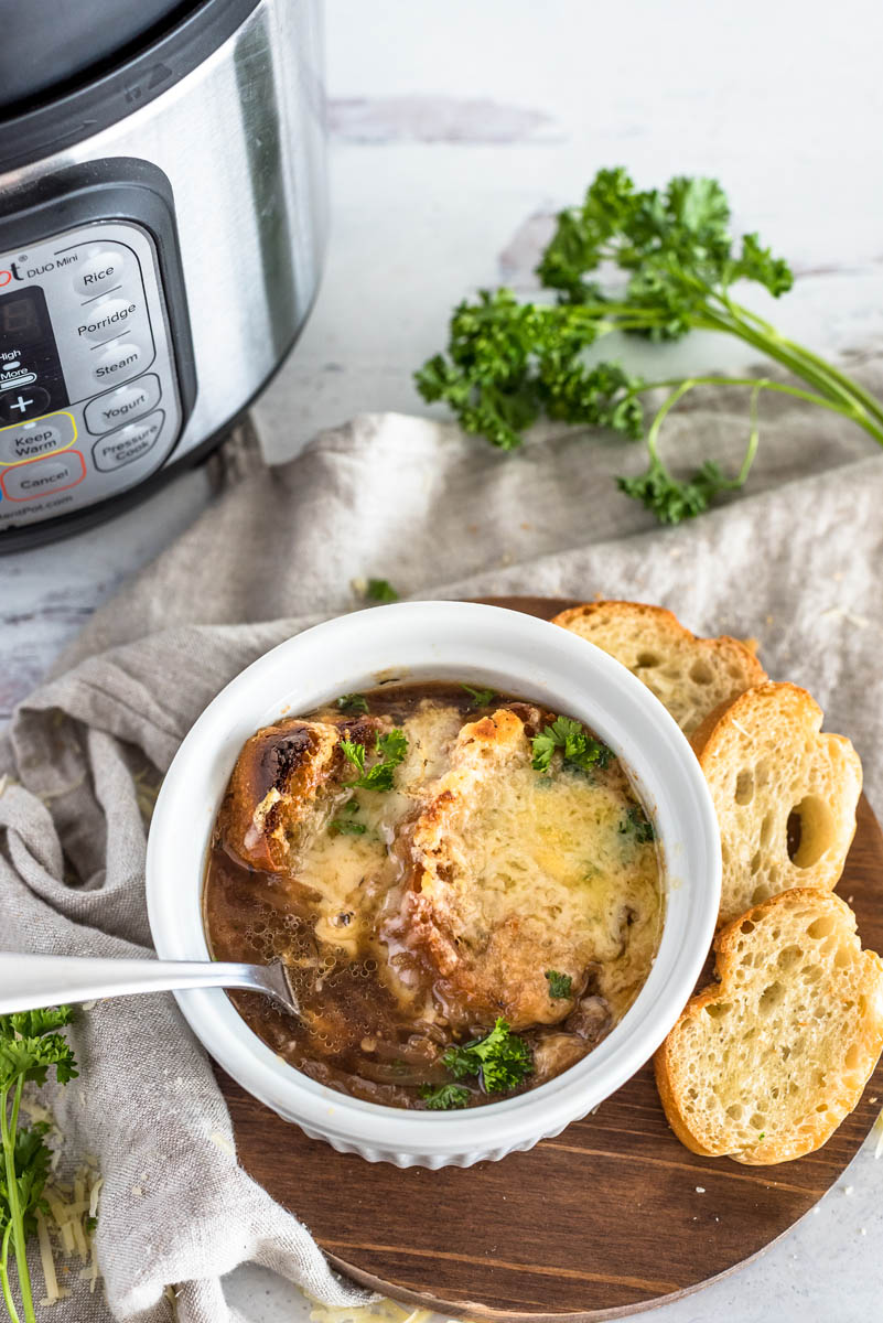An overhead shot of pressure cooker French Onion Soup dished up in a white ramekin with lots of browned bread and cheese on top, with additional slices of bread, parsley, and an INstant Pot in the background