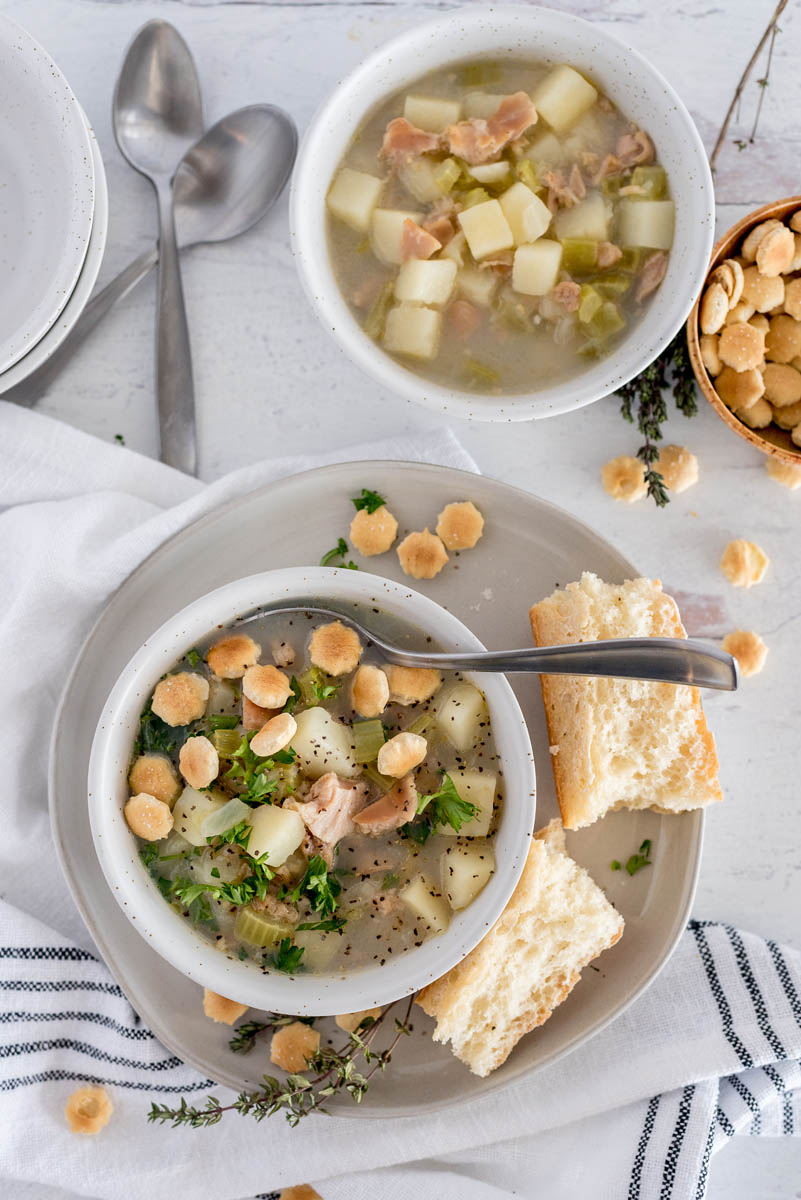 Overhead shot of Instant Pot light clam chowder garnished with oyster crackers and parsley, served in a white bowl with a roll.