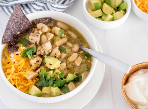bowl of instant pot white chicken chili with avocado, chips and shredded cheese on top