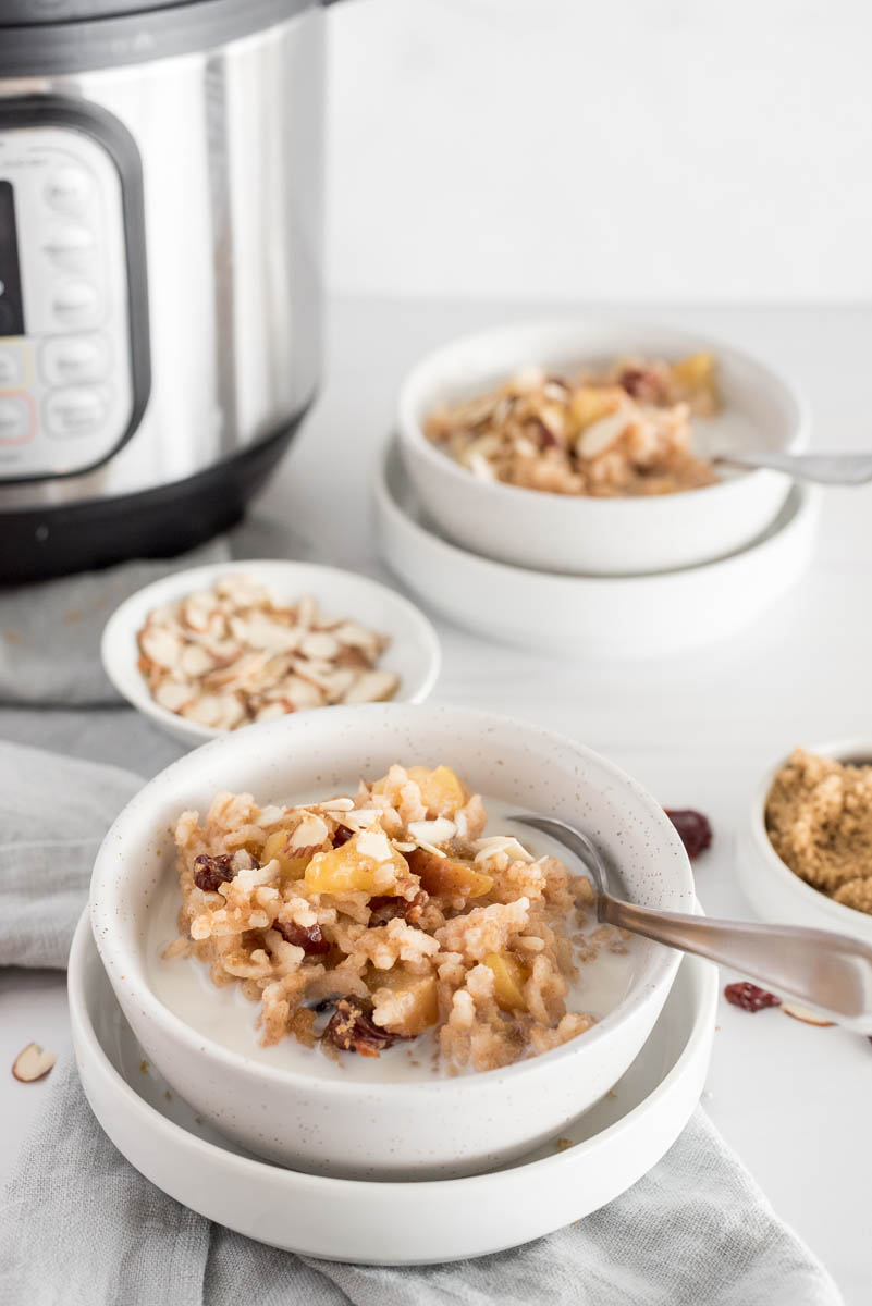 A vertical shot with an Instant Pot and bowls of almonds and cherries in the background with a white speckled bowl filled with breakfast apple risotto, garnished with diced cherries and a splash of milk, with a spoon on the side ready to eat