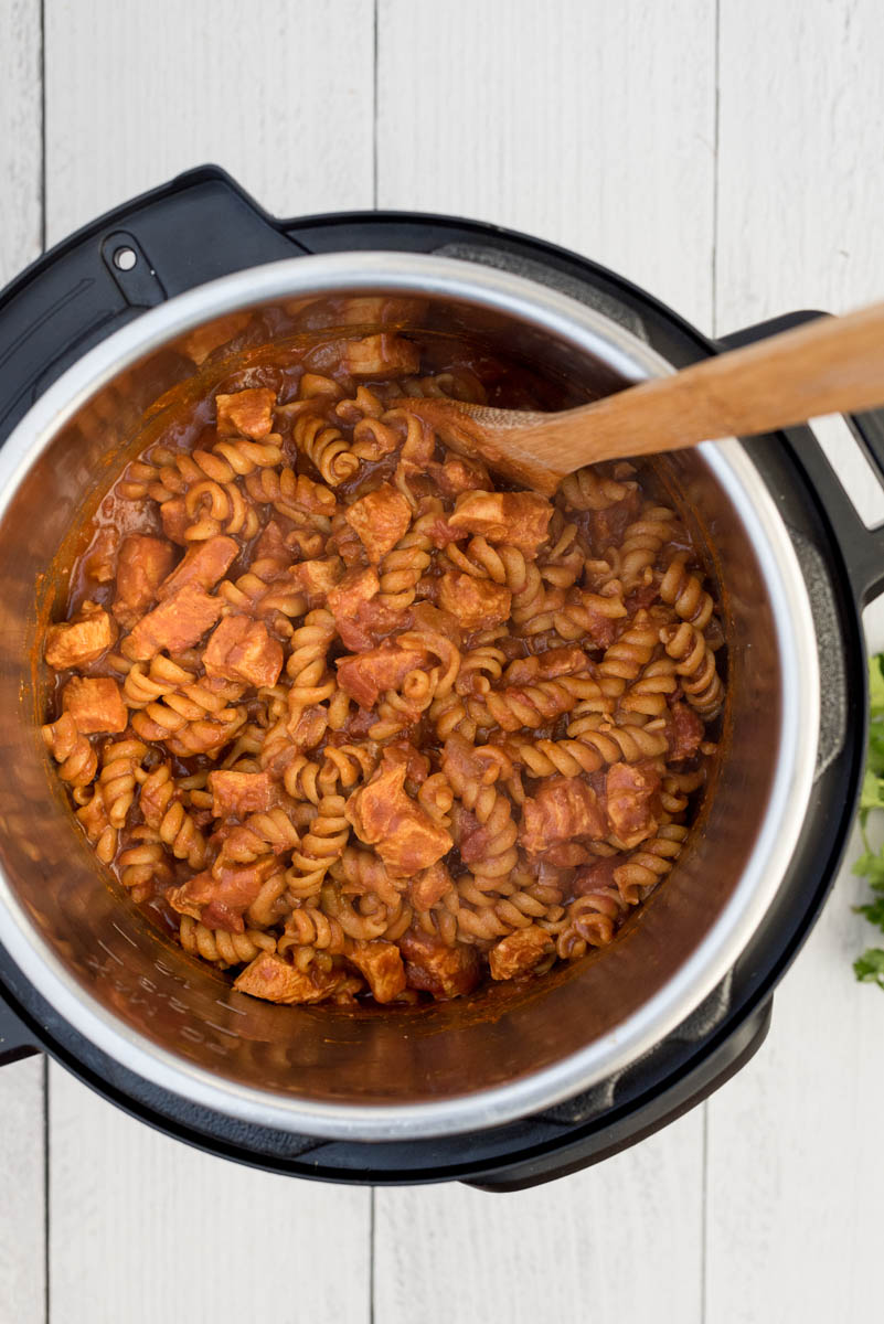 Overhead picture of chicken enchilada pasta cooked in an Instant Pot with a wooden spoon used for stirring.