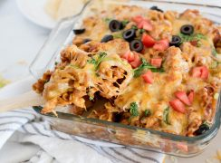 Instant Pot chicken enchilada pasta being scooped from a serving dish using a wooden spoon.