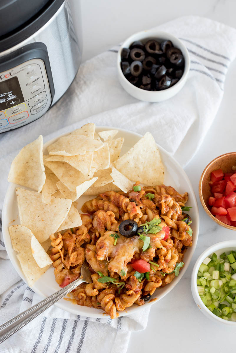 Pressure Cooker chicken enchilada pasta served on a plate with chips, with diced green onions, tomatoes, and sliced olives in bowls in front of an Instant Pot.