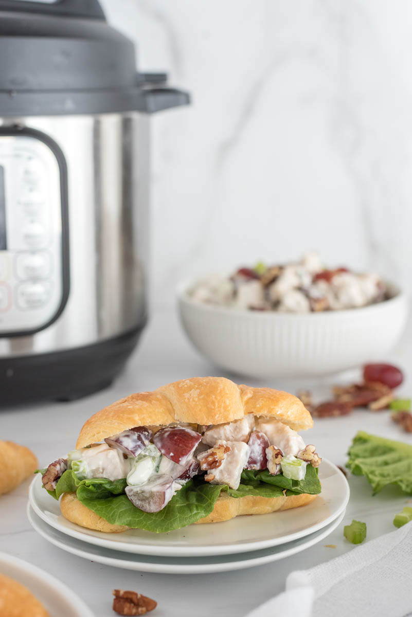 chicken salad sandwich on a plate in front of an instant pot pressure cooker