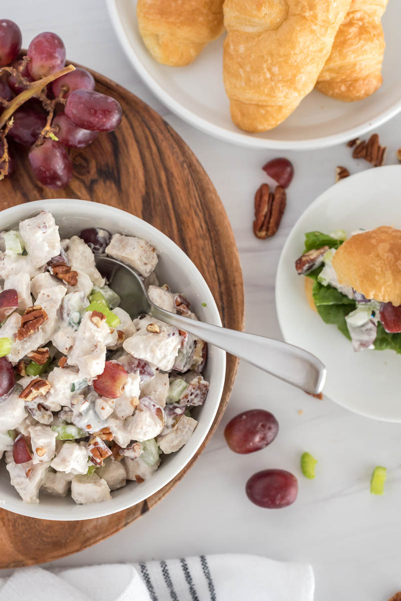 overhead of a white bowl with chicken salad and grapes, pecans and croissant rolls