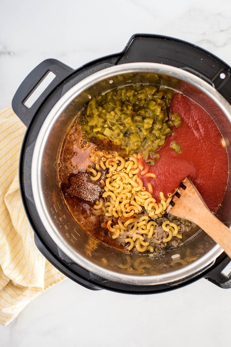 An overhead shot looking into an Instant Pot filled with macaroni, sausage, diced green chiles, and tomato sauce