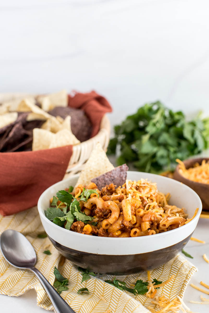A black and white bowl of Instant Pot chili mac, garnished with cilantro and blue and white corn chips, sitting on a yellow napkin with a spoon, with a basket of chips, additional cilantro, and cheese visible in the background