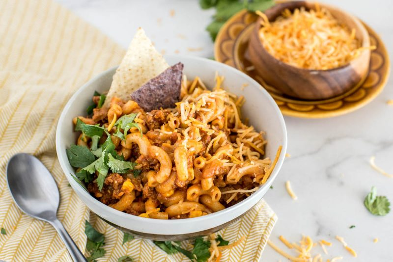 A close-up 45 degree shot of a white bowl of pressure cooker chili pasta, sitting on a yellow napkin garnished with cilantro, with a small bowl of grated yellow cheese visible in the background