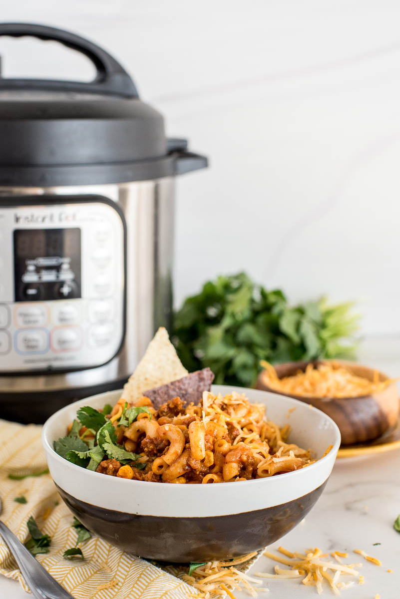 a direct shot of a black and white bowl of Instant Pot Chili Pasta with a cilantro garnish and white and blue corn chips, with an Instant Pot visible in the background