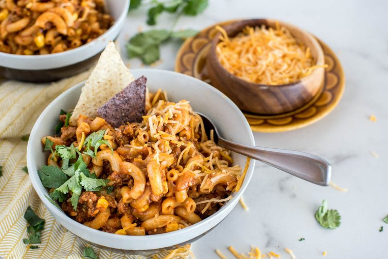 Close-up shot of Instant Pot Chili Pasta, served in a white bowl and garnished with cilantro, shredded cheese, and white and blue corn chips, with a bowl of shredded cheese in the background