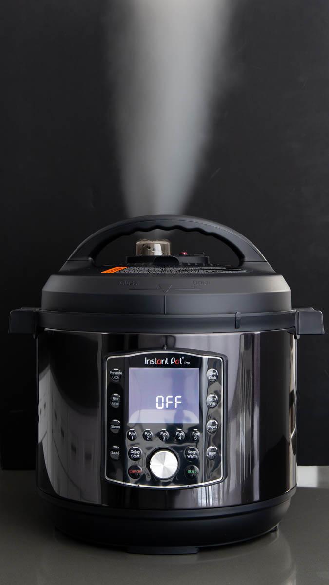 Instant Pot Pro steam release against a black background