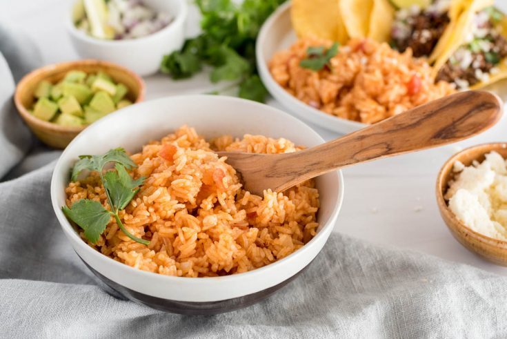 45 degree shot of Instant Pot spanish rice with a wooden serving spoon, garnished with parsley with a background of boowls of avocado, onions, and plate with beef tacos in the background