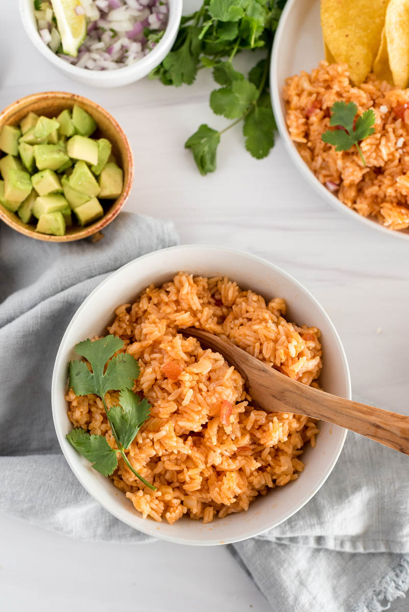 white bowl with spanish rice and green garnishes