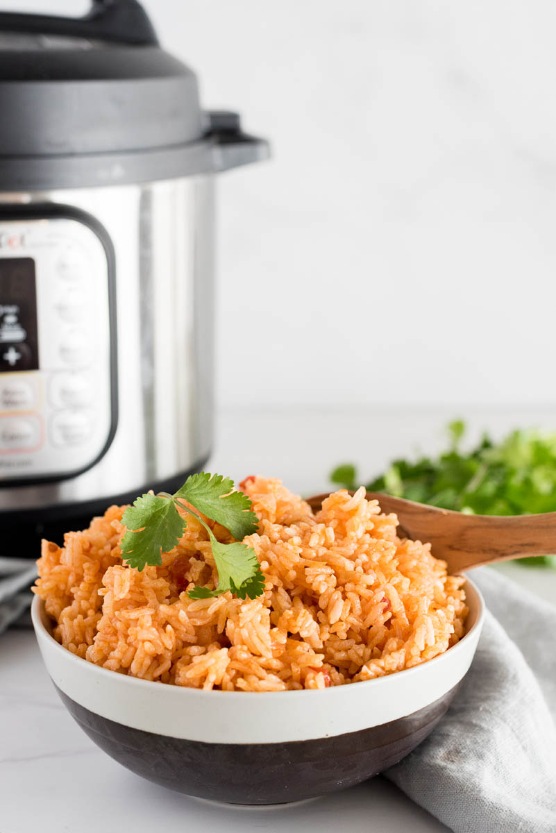 bowl of spanish rice with cilantro in front of an instant pot