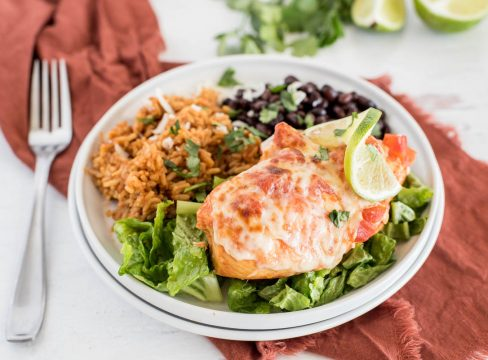 a 45 degree closeup horizontal shot of Instant Pot Salsa Chicken, plated on a white plate and served on top of a bed of shredded lettuce, with Mexican rice and black beans in the background