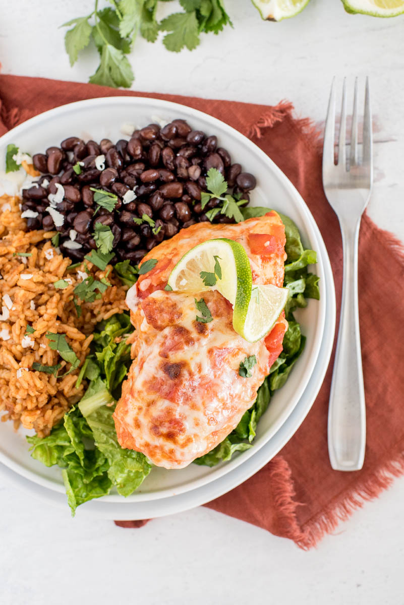 an overhead shot of pressure cooker Salsa Chicken, plated on a white plate garnished with a lime wedge and melty cheese, and served on top of a bed of shredded lettuce, with Mexican rice and black beans in the background