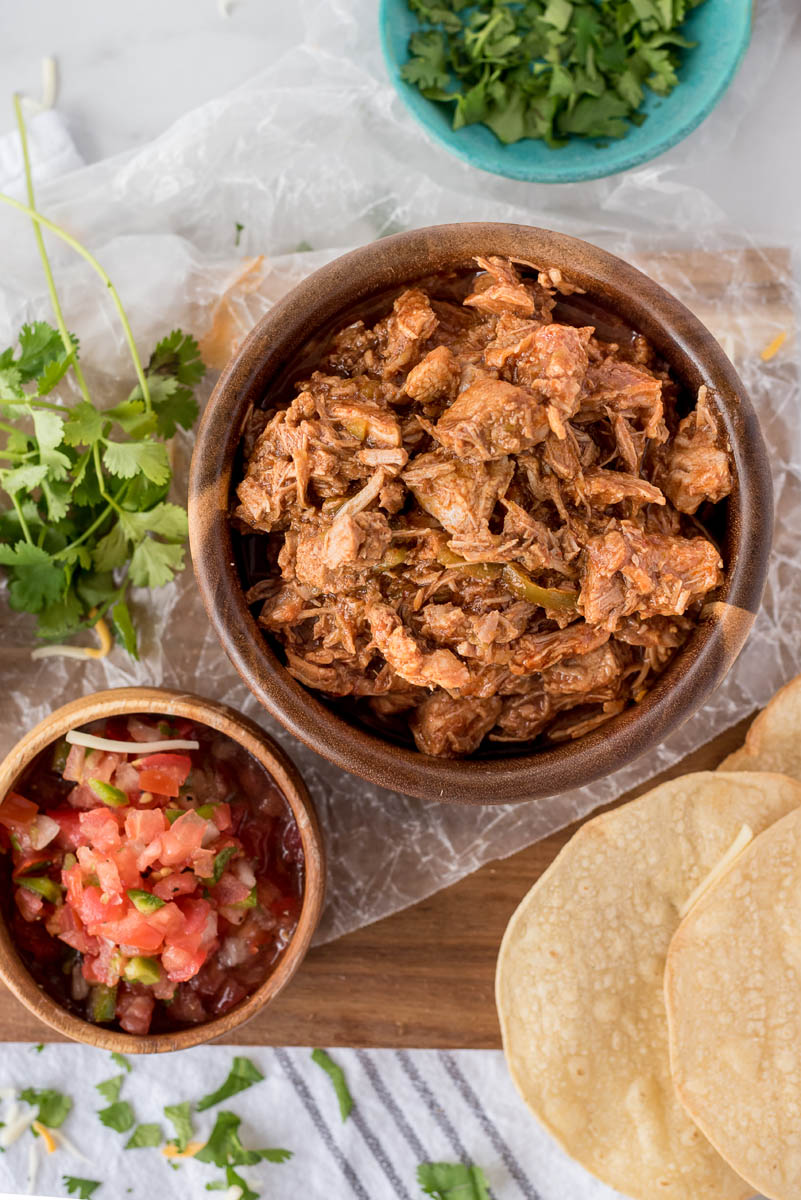 overhead of a bowl of sweet pork and a bowl of tomatoes salsa with crispy tortillas
