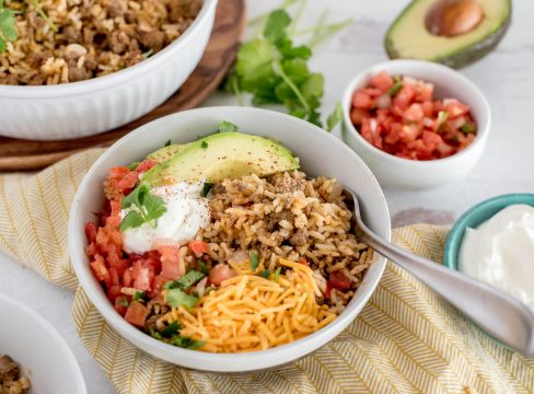 bowl of instnat pot taco rice with avocado, cheese, sour cream and tomatoes on top