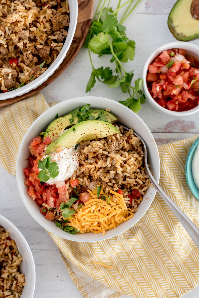 Overhead picture of Instant Pot taco rice topped with sliced avocado, cheese, cilantro, tomatoes, and sour cream. Placed in a white bowl with tomatoes, fresh cilantro, and a serving bowl with taco rice in the background.