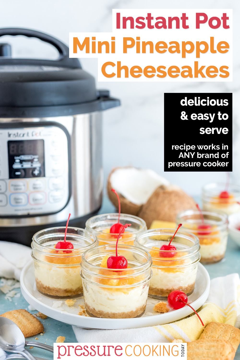 """A Pinterest image reading """"Instant Pot Mini Pineapple Cheesecakes"""" featuring a 45 degree shot of four mini mason jars filled with Instant Pot Coconut Cheesecakes, with a sweet pineapple topping and a maraschino cherry on top, with an Instant Pot, coconut, and pineapple visible in the background via @PressureCook2da"""
