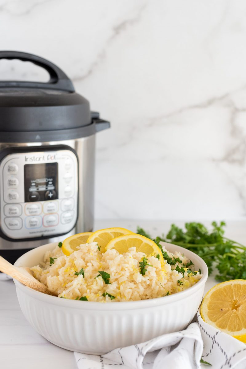 white bowl of lemon rice in front of an instant pot